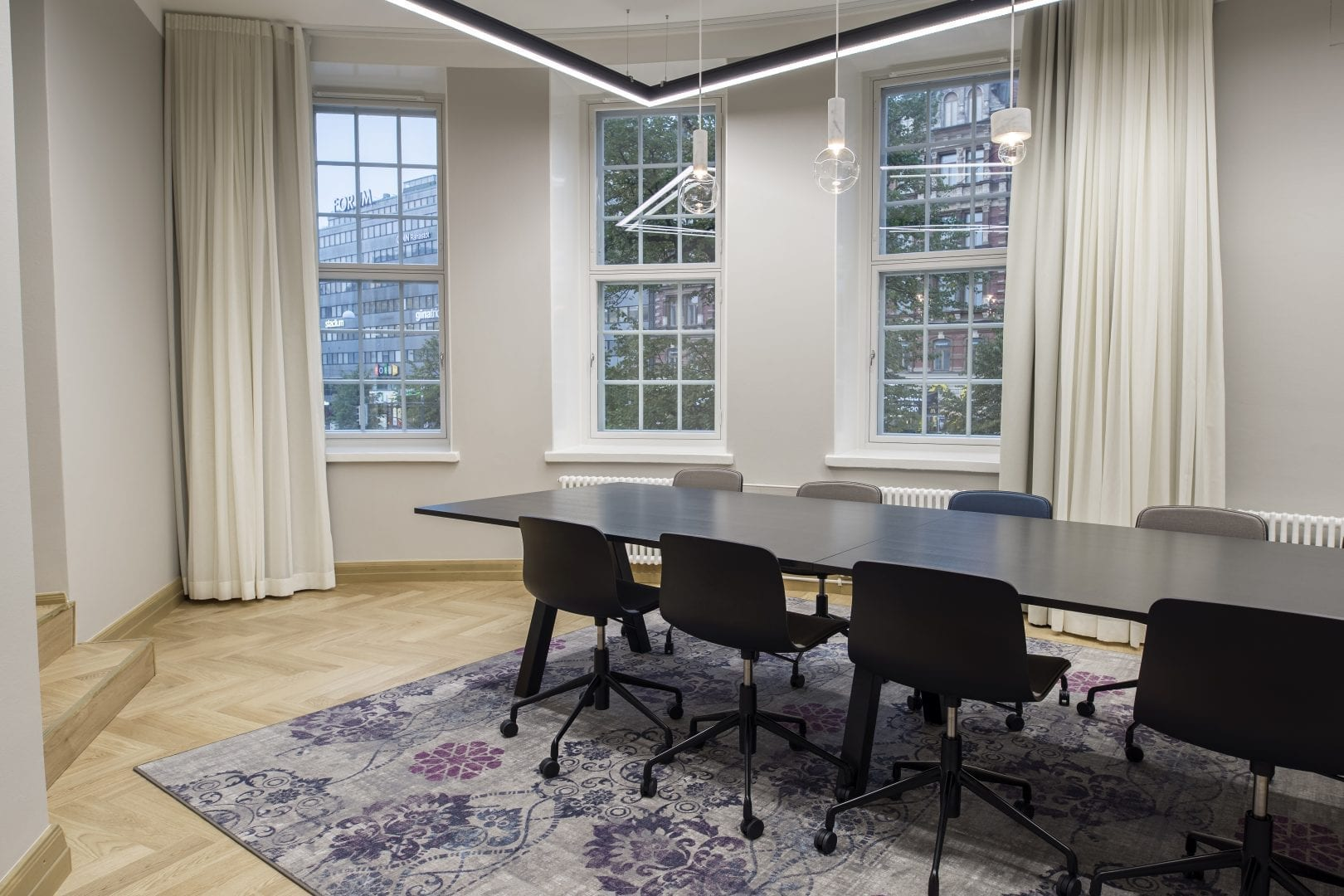 A photo from inside a light-colored meeting room. There's three tall windows with window sills and light long curtains on the sides. On the light wooden floor there's a light purple carpet. There's a black, long wooden desk and black chairs with wheels around it.