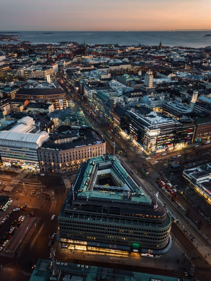 An aerial shot of Helsinki in dusk, taken from above the Postitalo building and Sokos next to the Railway Station. One can see the Mannerheimintie road and light traffic leading through the city toward the ocean.