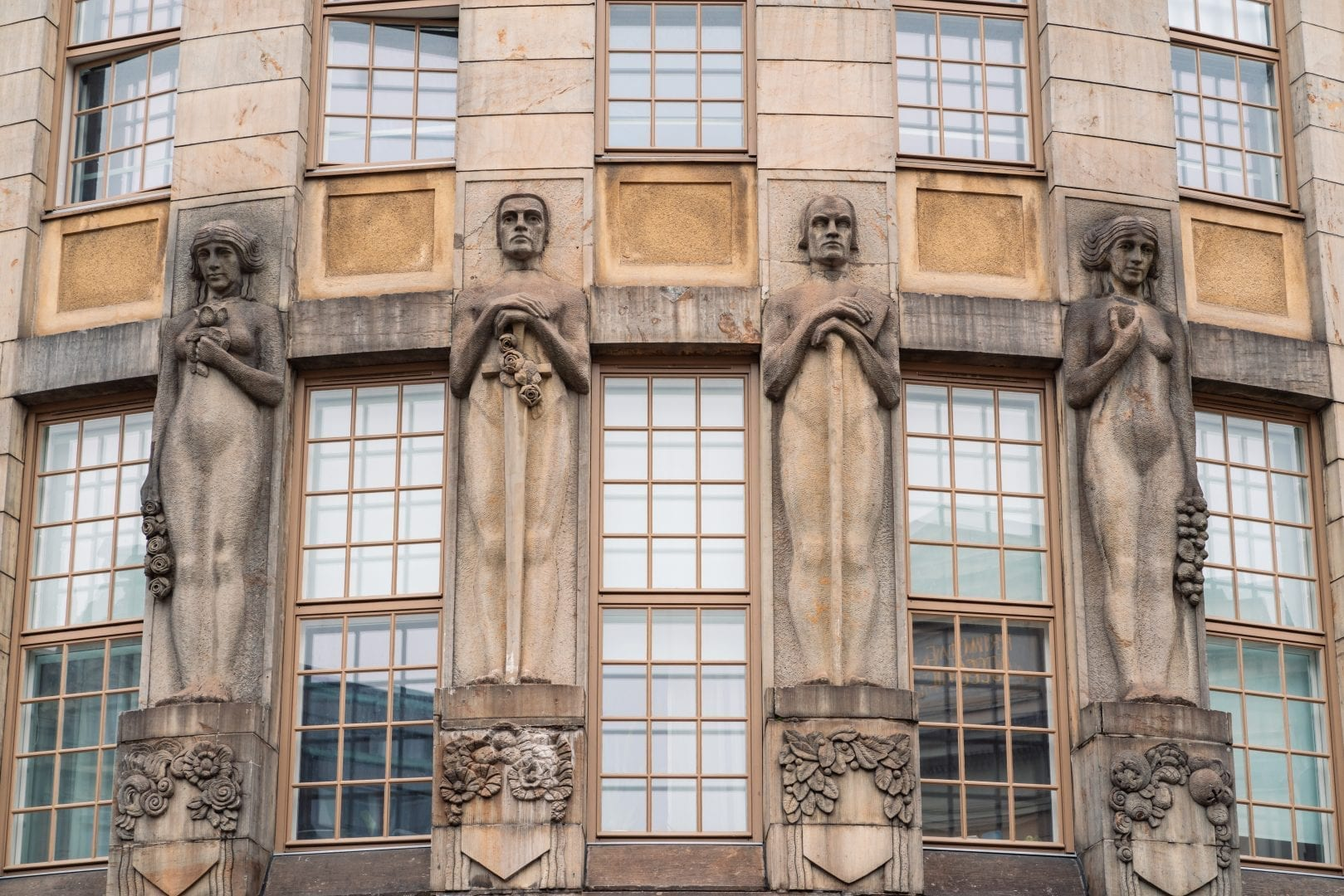 A close-up photo of an old building with very tall windows. There's four statues, one between every set of windows. From the left: a woman with short hair, naked, holding roses in one hand and a handful of flowers over her chest with the other, standing on a pedestal with rose and floral elements. A man with a sword held with two hands against his body, adorned with roses, with a stern face, naked, with morning glory-like florals on his pedestal. A man with a staff held with both hands against his body, naked, with leaves and small berries on his pedestal. A woman holding a large bunch of fruits in one hand, and a single apple over her chest, naked.