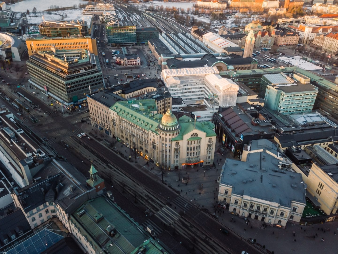 An aerial photo of the New Student House in central Helsinki. It is an old building in a shade of worn yellow with a green copper rooftop. The building is slightly L-shaped, with a tower in the corner. The round tower has an impressive, round dome. The photo also depics the surrounding city and the Central Railway Station in the back. It's winter, dusk.